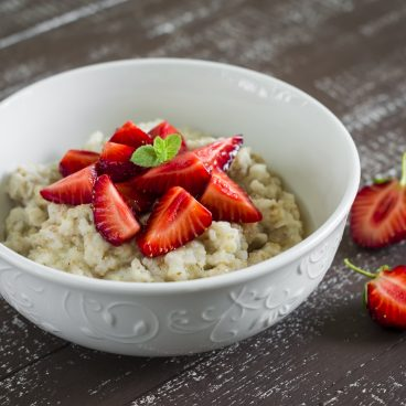 oatmeal with strawberries in a white bowl and orange juice on a dark wooden background