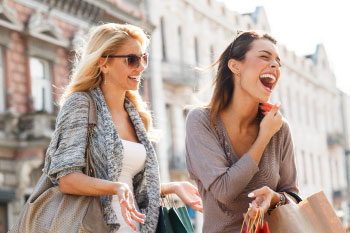 Women shopping bags laughing outside