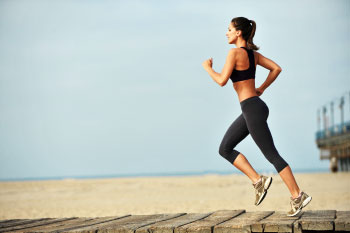 fit woman running on beach