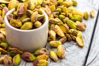 Pistachios in a bowl on a wood table