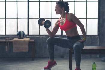 a woman holding a free weight in a gym