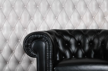 tufted black leather couch on grey leather background