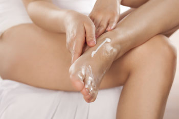 woman putting lotion on her feet