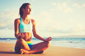 woman meditating at sunset on beach
