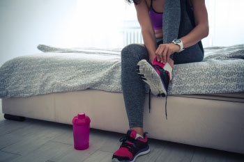 woman tying gym shoes sitting on bed