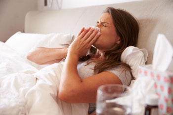 woman in bed sick with cold and flu