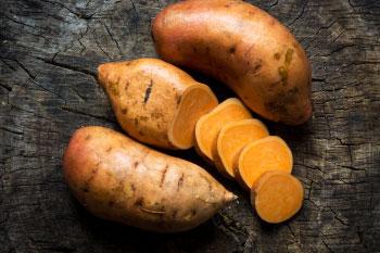 sweet potatoes on wood background