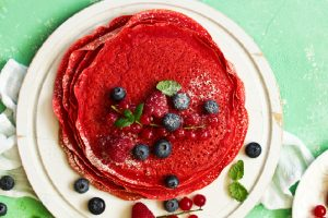 red velvet pancakes on white plate with fresh berries on top
