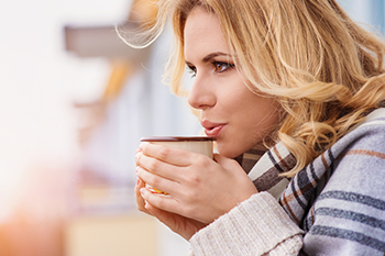 girl smiling holding hot chocolate raw cacao boosts health