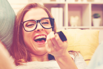 woman laughing at tv overcome loneliness holidays