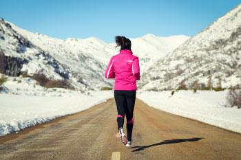 woman running in winter mountains reasons gain weight winter
