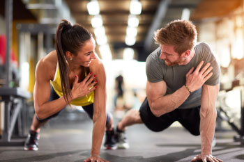 man and woman doing push up in gym men lose weight faster women