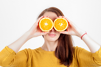 woman holding up orange slices foods boost eye health