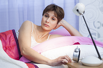 Sleep-deprived woman in bed reasons not losing weight
