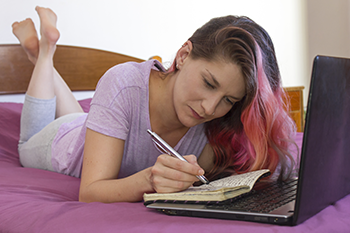 woman in bed writing stress affects body