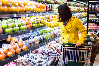 asian woman checking label produce supermarket
