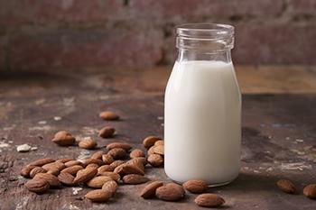 natural vertigo remedy almond seeds bottle of milk on table
