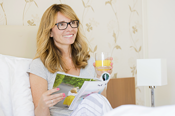 middle aged woman in bed drinking juice reading magazine brain weight loss