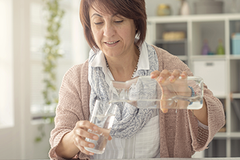 middle-aged woman pouring water to glass numbers track health