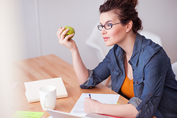 young woman working while eating healthy snacks
