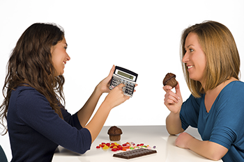 young women calculating calories weight loss myth