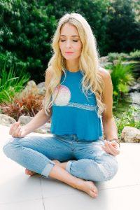 Danette May sitting meditating outside