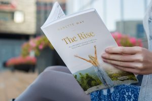 close up of a woman reading The Rise Book