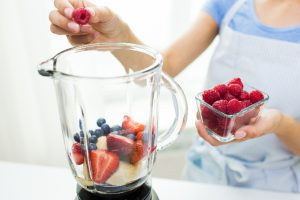 woman putting berries and banana in a blender