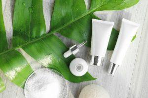 acne cream on green palm leaf