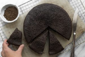 flourless chocolate cake on parchment lined cooling rack