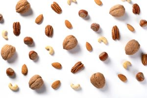 various kinds of nuts scattered on white background