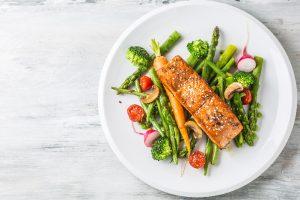 salmon on fresh veggies on a white dish