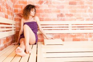 woman sweating sitting in a sauna