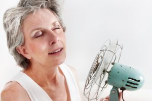 woman having a hot flash sitting by hand held fan