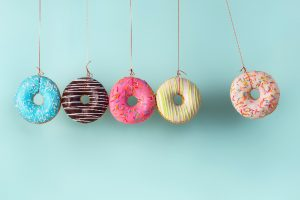 donuts hanging from strings on blue background sugar causes candida overgrowth