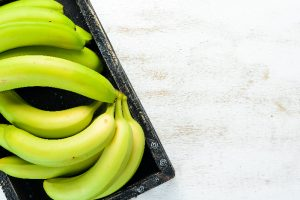 green bananas on white wood table probiotics weight loss